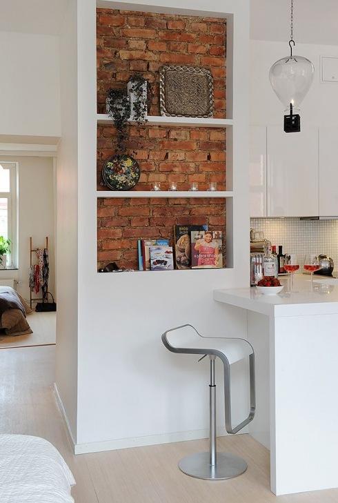 biała zabudowa z pólkami w kuchni ze ścianą cegły z