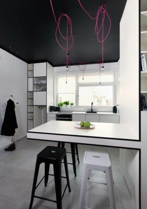 biała kuchnia z czarnym sufitem i oświetleniem z różowych