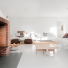 minimalistyczna aranżacja białego salonu z  kominkiem z czerwonej cegły