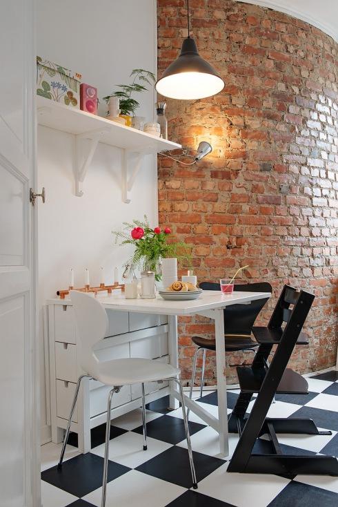 ściana z czerwonej cegły w kuchni,białe półki wiszące,rozkładany biały stół z   -> Kuchnia Biale Cegly