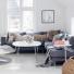 nowoczesny fotel z podnóżkiem,metalowy stolik z białym blatem,szary narożnik i grafitowa witryna w salonie