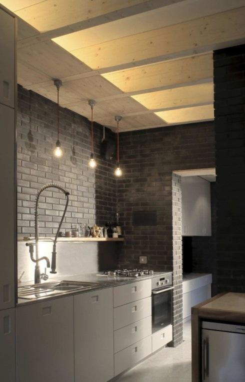 nowoczesna szara kuchnia z ciemnoszarą cegłą na ścianie, drewnianym sufitem i